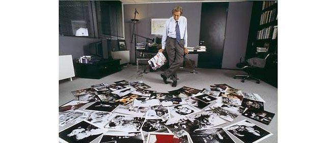 """Roger Thérond, directeur de """"Paris Match"""", dans son bureau avec les photos des 50 ans du magazine."""