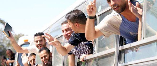 Des prisonniers libérés saluent la foule à leur arrivée à Gaza.