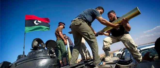 Des combattants anti-Kadhafi chargeant des pièces d'artillerie dans la bataille de Syrte.