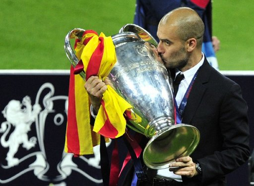 Barcelona's Spanish coach Josep Guardiola kisses the trophy at the end of the UEFA Champions League final football match FC Barcelona vs. Manchester United, on May 28, 2011 at Wembley stadium in London.Barcelona won 3 to 1. AFP PHOTO / GLYN KIRK