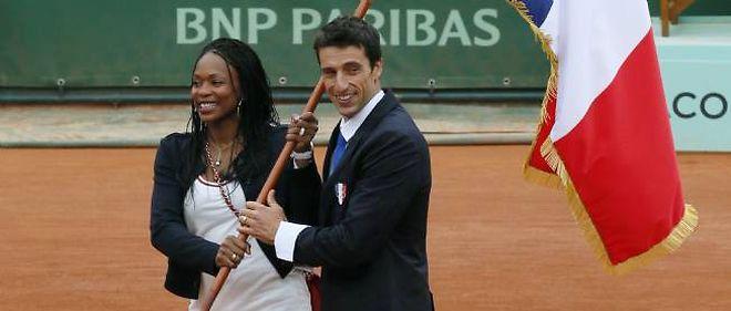 L'épéiste Laura Flessel, porte-drapeau de la délégation française aux JO de Londres, a reçu le drapeau tricolore des mains de son prédécesseur, Tony Estanguet, sur le Central de Roland-Garros, dimanche.