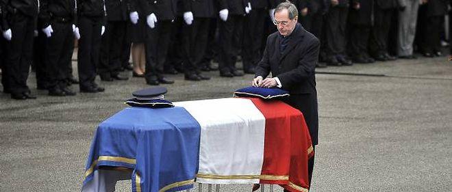 Claude Guéant décore de la Légion d'honneur à titre posthume le policier Cédric Pappatico lors d'une cérémonie dans la cour d'honneur de la préfecture de Chambéry, le 14 avril 2012.