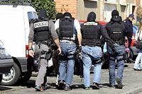 Des policiers encerclent l'immeuble où vivait  Mohamed Merah à Toulouse, le 23 mars 2012. ©JEAN-PIERRE MULLER