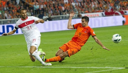 Netherlands' Robin van Persie (R) vies for the ball with Turkey's Omer Toprak (L) during their FIFA 2014 World Cup qualifying football match in Amsterdam on September 7, 2012. AFP PHOTO / ANP / TOUSSAINT KLUITERS **NETHERLANDS OUT**