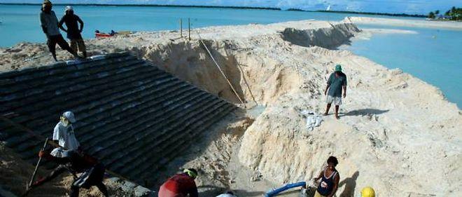 Des ouvriers construisent une digue sur une île des Kiribati.