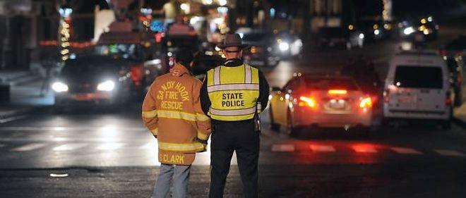 Un pompier et un policier sur la route qui mène à l'école de Sandy Hook, où a eu lieu une terrible fusillade le 14 décembre, entraînant la mort de 27 personnes.
