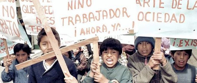 """Manifestation d'enfants le 1er mai à La Paz. Sur les pancartes : """"Vive l'enfant qui travaille"""" et """"Nous aussi faisons partie de la société""""."""