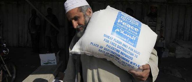 Un Palestinien transportant un sac de nourriture distribué par l'UNRWA.