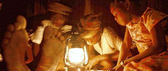Des enfants font les devoirs de classe à la lampe à pétrole.