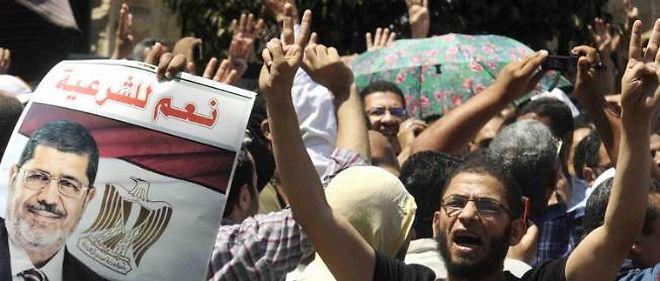 Un homme fait le signe de paix, alors que pro et anti-Frères musulmans s'opposent en Égypte.