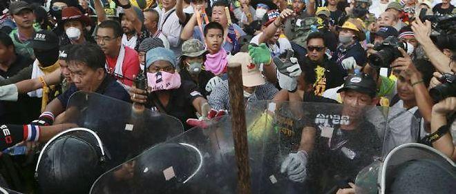 """Les """"chemises jaunes"""", des manifestants antigouvernementaux, font face aux forces antiémeute à Bangkok, le lundi 25 novembre. © Wason Wanichakorn / Sipa"""