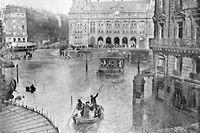 Des Parisiens gagnent en barque à la fin de l'année 1910, sur la Cour de Rome à Paris, la Gare Saint-Lazare, cernée par la crue de la Seine. L'inondation de 1910 fut la plus importante du 20e siècle à Paris. ©Intercontinentale