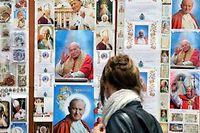 Une femme regarde des représentations de Jean-Paul II sanctifié, au Vatican. ©ALBERTO PIZZOLI / AFP