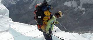 Un sherpa portant un énorme sac passant sur échelle dans l'Everest. ©DR