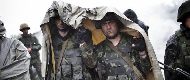 Des soldats ukrainiens se protégeant de la pluie aux abords d'une barricade aux alentours de la ville de Slaviansk, le 2 mai 2014.