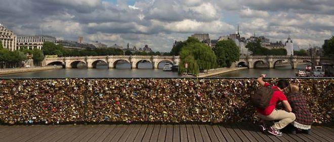 Les touristes accrochent des cadenas sur le célèbre pont parisien.