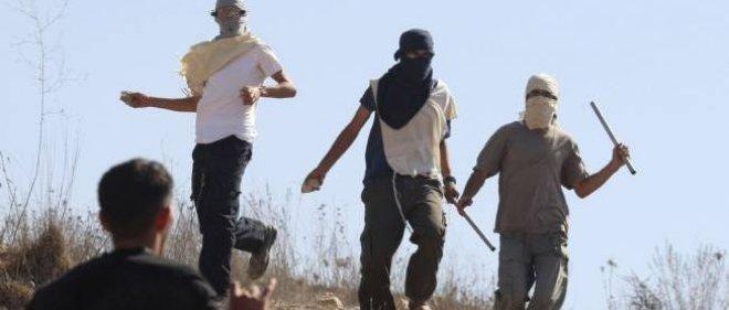 Des colons juifs masqués (en haut de la photo) prêts à en découdre avec des habitants du village palestinien d'Assira, en septembre 2011, en Cisjordanie.