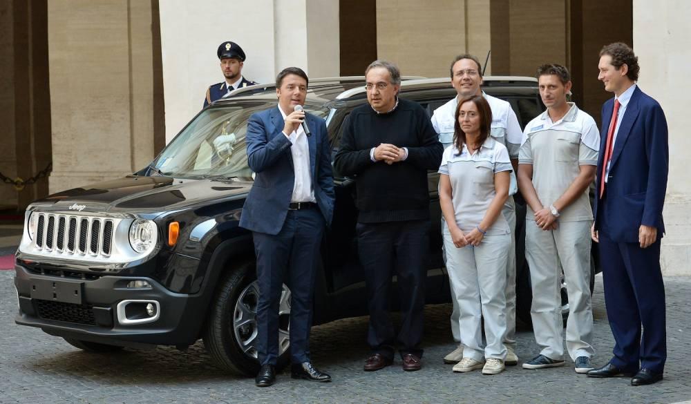 Les ouvriers italiens (en blanc) peuvent être inquiets sur l'avenir de leur usines en Italie, malgré les assurances affichées par lesleaders de la marques devant Matteo Renzi ©  AFP