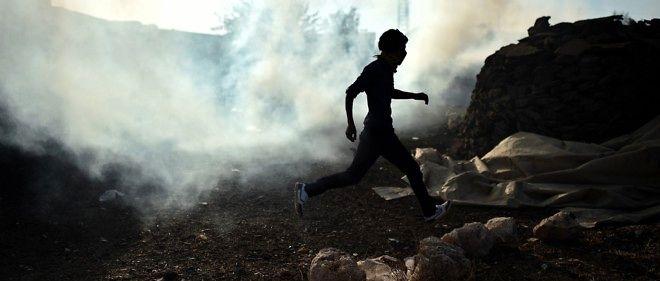 Un Kurde fuit les gaz lacrymogènes lancés par la police dans le village turc de Mursitpinar, près de la ville syrienne de Kobané.
