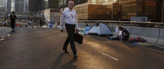 Un homme se rend sur son lieu de travail à Hong Kong alors qu'en arrière-plan quelques manifestants pro-démocratie restent mobilisés.