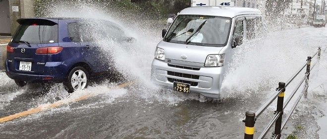 Des véhicules avancent avec peine dans une rue inondée de la ville de Chiba, près de Tokyo, après le passage du puissant typhon Phanfone.