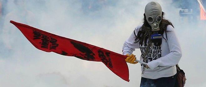 Un manifestant tient un drapeau au milieu des gaz lacrymogènes à Ankara.