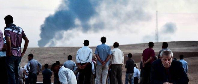 Des Kurdes regardent vers Kobané depuis la frontière turco-syrienne.