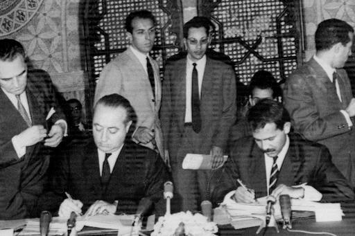 Le secrétaire d'Etat français aux Affaires algériennes, Jean de Broglie (g), et le ministre algérien des Affaires étrangères Abdelaziz Bouteflika signent, le 29 juillet 1965 à Alger, l'accord franco-algérien sur les hydrocarbures, clé de voûte de la coopération entre les deux pays ©  AFP/Archives