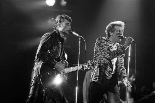 Les chanteurs Johnny Hallyday (g) et Eddy Mitchell sur la scène du 9ème Printemps de Bourges, le 1er avril 1985 © Frank Perry AFP/Archives