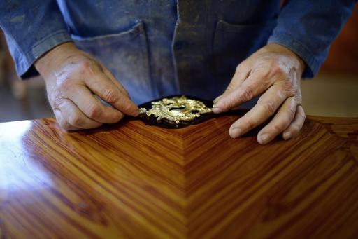 Un employé des ateliers Allot, à Loudéac, en Bretagne, travaille à la confection d'un meuble d'époque, le 7 octobre 2014 © Jean-Sébastien Evrard AFP