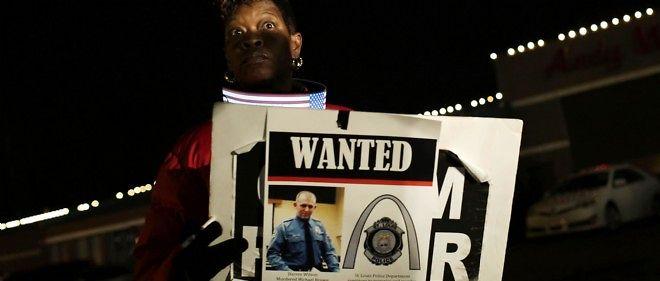 Une femme tient une pancarte représentant Darren Wilson, le policier qui a tué début août le jeune Michael Brown.