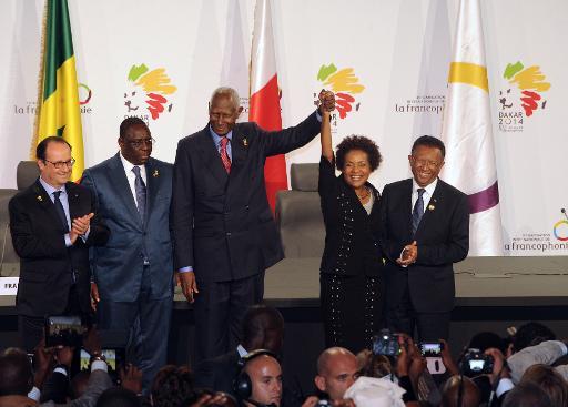 Abdou Diouf (c. g.) lève le bras de la Canadienne Michaëlle Jean, désignée pour lui succéder à la tête de la Francophonie, lors du congrès de l'organisation, le 30 novembre 2014 à Dakar © Sow Moussa AFP