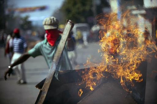 Mise en place d'une barricade lors d'une manifestation anti-gouvernementale le 13 décembre 2014 à Port-au-Prince © Hector Retamal AFP