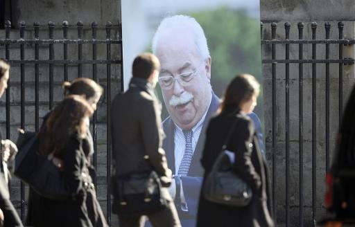 Des passants devant le portrait de Christophe de Margerie, à l'Eglise Saint-Sulpice à Paris, le 27 octobre 2014, jour de ses obsèques © Stéphane de Sakutin AFP/Archives