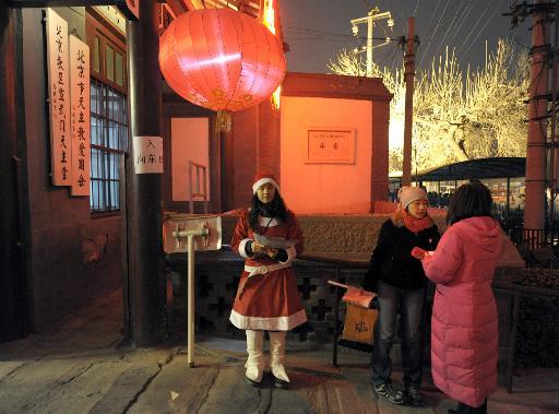 Une femme en costume de Père Noël se tient à l'entrée d'une église à Pékin, le 24 décembre 2009 © Liu Jin AFP/Archives