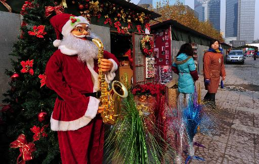 Une figurine taille réelle du père Noël jouant de la trompette est exposé devant un stand de décorations dans une rue de Pékin, en 2010 © Frederic J. Brown AFP/Archives