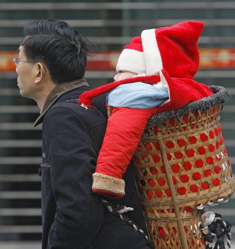 Un homme transporte dans un panier traditionnel son bébé habillé en père Noël © Liu Jin AFP/Archives