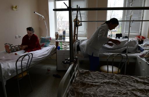 Une infirmière au milieu de blessés lors de combats dans l'est de l'Ukraine, le 19 décembre 20104 à l'hôpital de Donetsk où elle a été opérée © Vasily Maximov AFP
