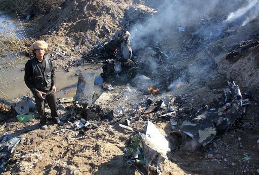 Un membre du groupe Etat islamique parmi les débris de l'avion d'un pilote jordanien, dans la région de Raqa, en Syrie, le 24 décembre 2014 © STR RMC/AFP