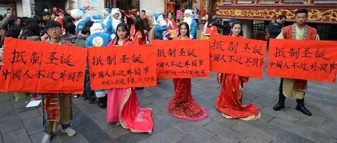 """Des étudiants chinois portent des bannières exhortant les riverains à """"résister à Noël"""", assurant que """"le peuple chinois ne devrait pas célébrer des fêtes étrangères""""."""