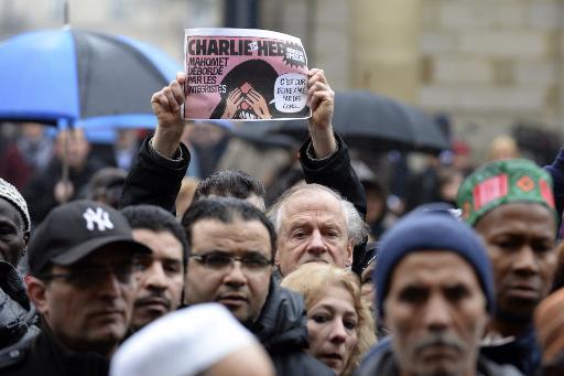 Un homme brandit une ancienne Une du journal Charlie Hebdo comportant une caricature du prophète Mahomet, le 9 janvier 2015 à Bordeaux © Jean-Pierre Muller AFP/Archives