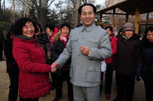 L'acteur chinois Xu Ruilin (g), sosie de Mao Tsé-toung, fondateur de la Chine populaire, pose avec un groupe d'admirateurs, le 27 janvier 2015 à Liaocheng, dans la province du Shandong ©  AFP