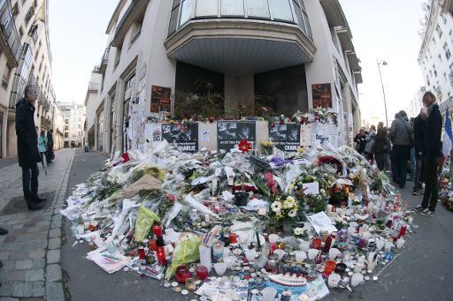 Des fleurs en hommage aux victimes déposées devant le journal Charie Hebdo le 11 janvier 2015 à Paris © Joël Saget AFP