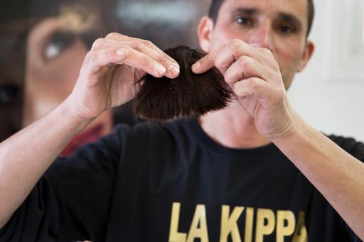 """Le coiffeur israélien Shalom Koresh montre sa """"kippa en cheveux"""", le 3 février 2015 dans son salon à Rehovot © Menahem Kahana AFP"""