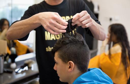"""Le coiffeur Shalom Koresh accroche sur le crâne d'un jeune Israélien sa """"kippa en cheveux"""", le 3 février 2015 à Rehovot © Menahem Kahana AFP"""