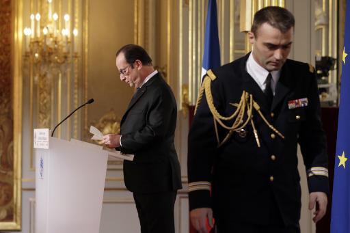 Le président Francois Hollande lit une note que lui apportée son aide de camp, pendant sa conférence de presse le 5 février 2015 à l'Elysée à Paris © Philippe Wojazer Pool/AFP