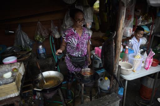 Une femme prépare un repas dans un petit restaurant d'un quartier défavorisé de Bangkok, le 26 janvier 2015 en Thaïlande © Christophe Archambault AFP