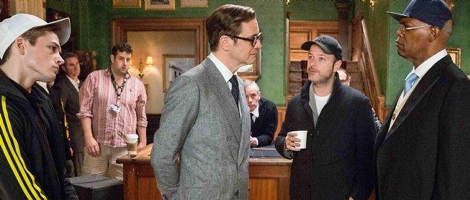 """Le réalisateur Matthew Vaughn (au centre) sur le tournage de """"Kingsman"""" avec Colin Firth, Samuel L. Jackson et Taron Egerton."""