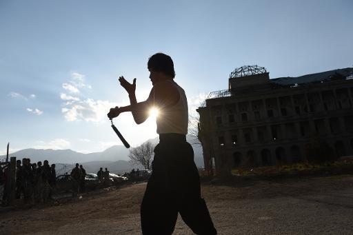 Abbas Alizada s'entraîne avec des nunchakus dans les ruines du palais de Darulaman, à Kaboul, le 8 février 2015 © Shah Marai AFP