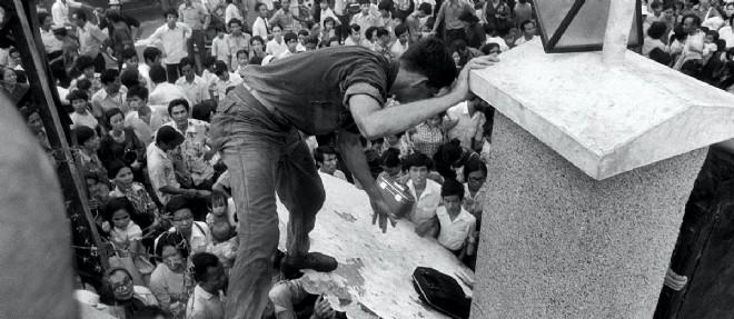 Des civils sud-vietnamiens tentent d'escalader les murs de l'ambassade americaine a Saigon le 25 avril 1975.